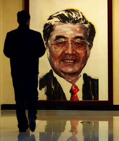 A man walks in front of a large-scale portrait of Chinese President Hu Jintao for the G20 Summit Leaders Portrait Exhibition at the Beijing Bridge Art Center on March 31, 2009.