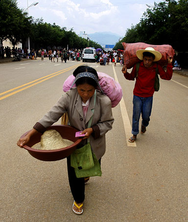 Burmese refugees on their way home to Burma walks towards the border gates in Nansan in southwestern China's Yunnan province, Monday, Aug. 31, 2009