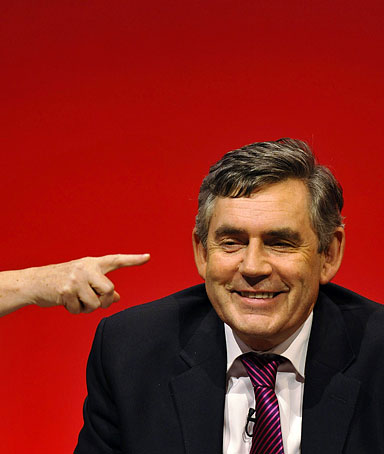 Britain's Prime Minister Gordon Brown smiles as he listens on stage during the annual Labour Party Conference in Brighton