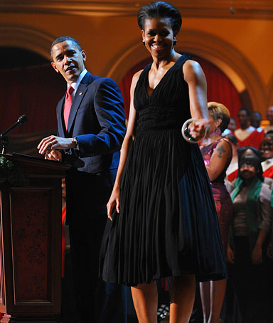 US President Barack Obama speaks as First Lady Michelle Obama gestures