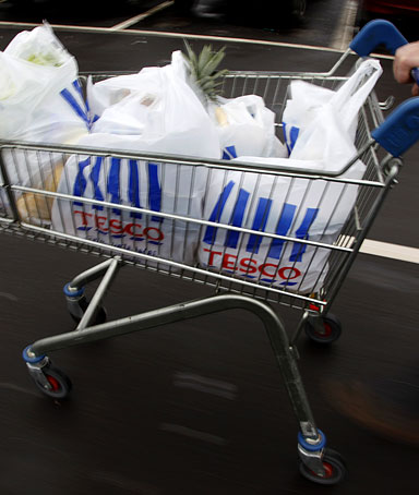 A man pushes a shopping trolley as he leaves a Tesco supermarket