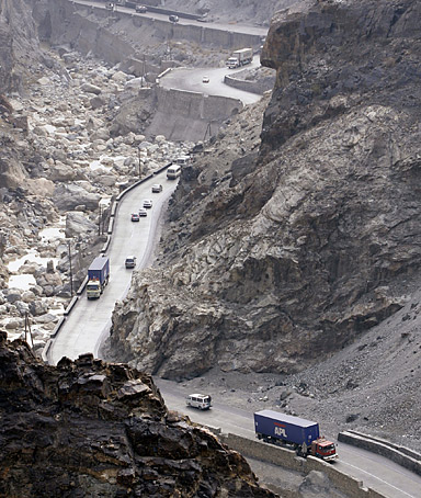 Trucks carry materials for foreign soldiers are seen on a high way in Surobi district of Kabul, Afghanistan on Wednesday, Dec. 17, 2008. Traveling in a convoy of 30 supply trucks escorted by security guards, the young Afghan driver hauled