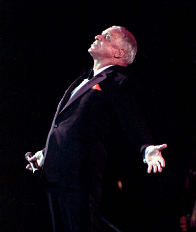 Sinatra bends backward as he recognizes the applause by a Filipino audience during the start of his four-day concert in Manila in 1994