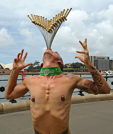 Internationally renowned street performer Chayne Hultgren, re-enacts his 18-sword swallowing attempt for a Guinness World Record in front of the Sydney Opera House on February 8, 2010