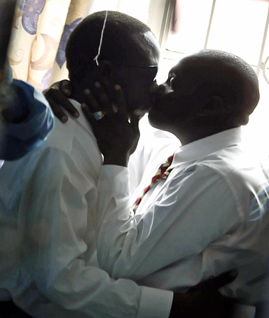 Nairobi, KENYA:  Gay men kiss 20 June 2006 in Nairobi. In Kenya, homosexuality is regarded as a crime and though a growing phenomenon, the movement is still secretive and the subject of numerous discriminations.