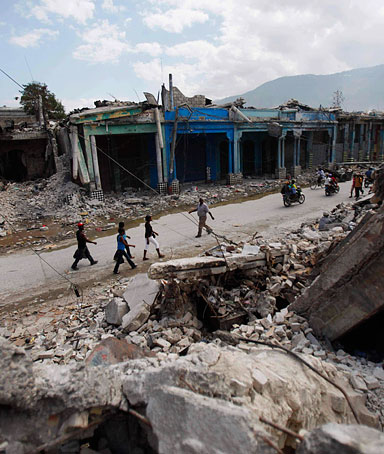 People walk in front of debris in Port-au-Prince, Sunday, Jan 31,  2010.