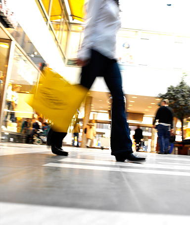 Low section view of a woman carrying a shopping bag in a shopping mall