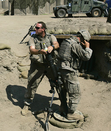 Specialist Chris Milam of Duncan, Oklahoma, left, puts in a shell inside an 81 mm mortar tube to fire at suspected Taliban fighters who crossed over from Pakistan into Korangal valley in Eastern Afghanistan, from a base in Kandagal on Sept. 7, 2006