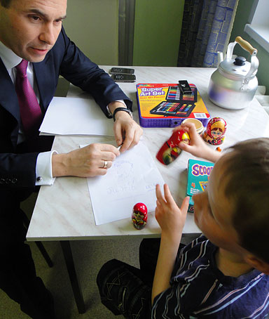 Pavel Astakhov, the Russian president's ombudsman for children's rights, plays with Artem Savelyev, 7, at Moscow's No 21 Children's Hospital