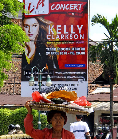 A food vendor walks past a banner promoting a Kelly Clarkson concert sponsored by a cigarette brand L.A. Lights, in Bogor, West Java, Indonesia