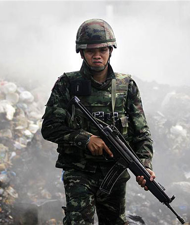 A soldier carries his weapon during an operation to evict anti-government