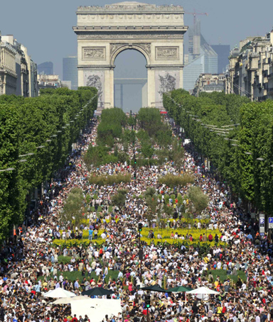 Visitors walk on the Champs Elysees near the Arc de Triomphe monument in Paris May 23, 2010.