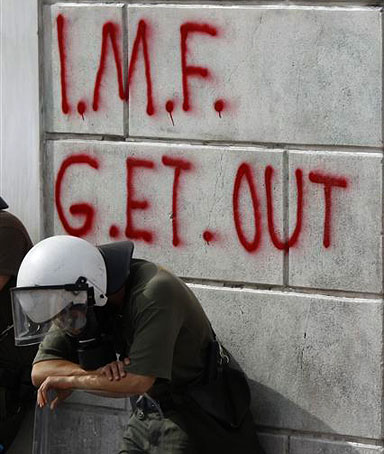 Greek riot policemen rest in front of graffiti written on the wall of a bank in Athens.