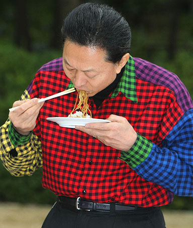 In a picture taken on April 4, 2010, Japanese Prime Minister Yukio Hatoyama eats noodles during a meet-the-people barbecue clad in a multi-coloured shirt at his official residence in Tokyo.