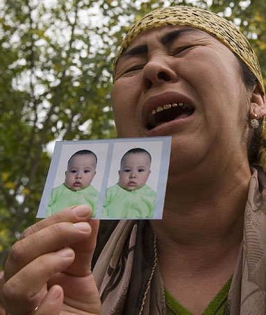 An ethnic Uzbek refugee, who fled from clashes in Osh, shows photos of her missing grandsons as she stands on the Kyrgyz-Uzbek border, after escaping to Uzbekistan, on June 15, 2010.