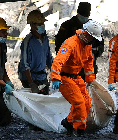 Rescue workers check the body of a miner who died after an explosion in a coal mine in Amaga, Antioquia province June 17, 2010