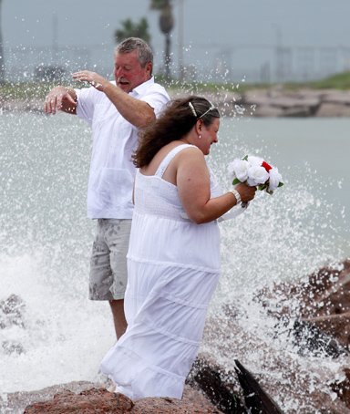 Dan and Grace Eaton are splashed by waves as they pose for a wedding photo