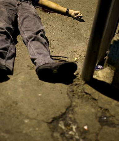 An unidentified man lies dead on the street in the neighborhood of Boleita in Caracas, November 15,2008. Venezuela has one of the world's highest murder rates