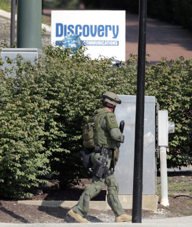 Armed police surround the area near the Discovery Channel headquarters building during a hostage situation in Silver Spring, Maryland September 1, 2010