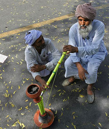 Muslim men smoke a hookah during a protest under the banner of
