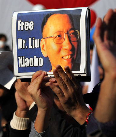 A protester holds a portrait of Chinese Nobel Peace Prize winner Liu Xiaobo during a rally against Chinese government in Tokyo, Japan, Saturday, Nov. 6, 2010.