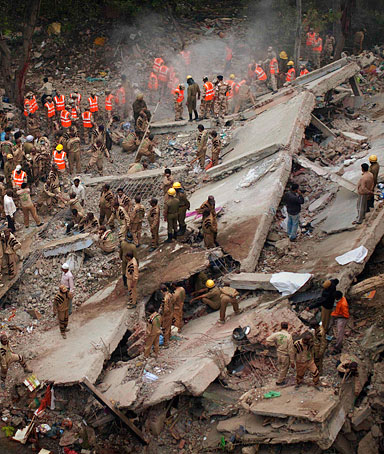 Rescue workers search amid debris after a four-story apartment building collapsed in New Delhi, India, Tuesday, Nov.16, 2010