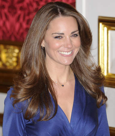 Kate Middleton enters a room with her fiance, Britain's Prince William, to pose for a photograph in St. James's Palace, central London November 16, 2010