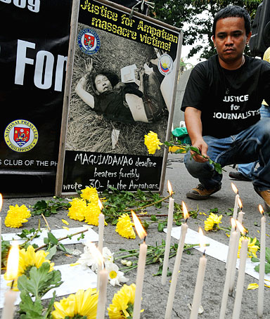 Philippine journalists offers flower and light candles in Manila on November 23, 2010 to remember the 57 people killed in the November 23, 2009 massacre in Maguindanao province in the southern Philippines