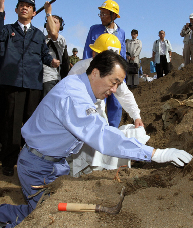Japanese Prime Minister Naoto Kan collects remains as he visits Iwoto Island, also known as Iwojima, to inspect the government's ongoing efforts to recover the remains of Japanese soldiers who died in World War II, December 14, 2010