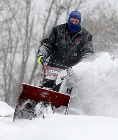 Terry Alspach, uses a snow blower to clear his driveway in Medina Township, Ohio, December 13, 2010