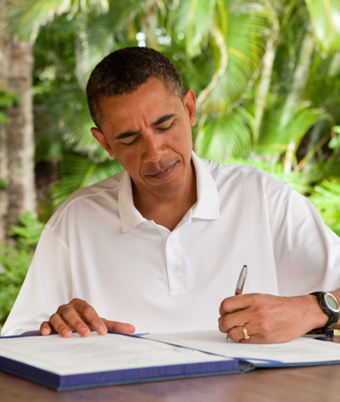 In this handout image provided by the White House, U.S. President Barack Obama signs H.R. 847, the