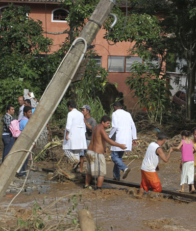 Residents cross a street affected by a landslide in Teresopolis January 12, 2011