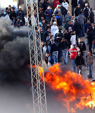 Protesters clash with riot police in Cite Ettadhamen near the Tunisian capital Tunis January 12, 2011