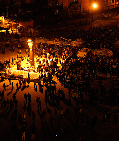 Protesters gather around army vehicles at Tahrir Square in Cairo February 6, 2011, to prevent the army from moving towards the square and placing barbed wires.