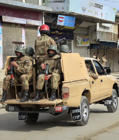 Soldiers patrol past shopkeepers after a suicide bomber struck a paramilitary training centre in Mardan, northwest Pakistan February 10