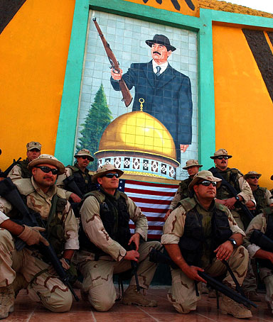 Members of a U.S. Navy combat unit pose April 6, 2003 under a Saddam Hussein mural in the Iraqi port town of Umm Qasr, Iraq