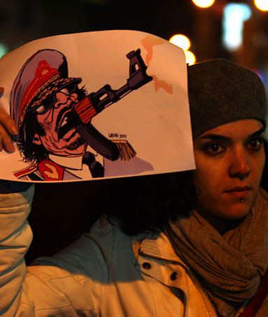 Palestinian demonstrators hold up placards during a protest in support of the Libyan people and calling for the ouster of Libyan leader Moamer Khadafi on February 22, 2011 in the West Bank city of Ramallah.