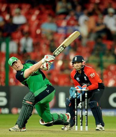 Ireland's Kevin O'Brien hits a six off the bowling of England's Graeme Swann (not in picture) watched by Matt Prior (R) during the ICC Cricket World Cup group B match in Bangalore March 2, 2011