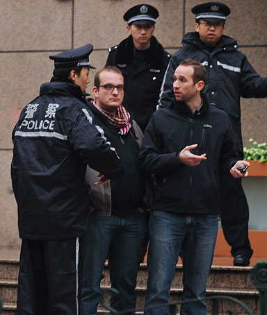 Foreign journalists are detained by Chinese policemen in a street leading to a designated demonstration site in Shanghai on March 6, 2011