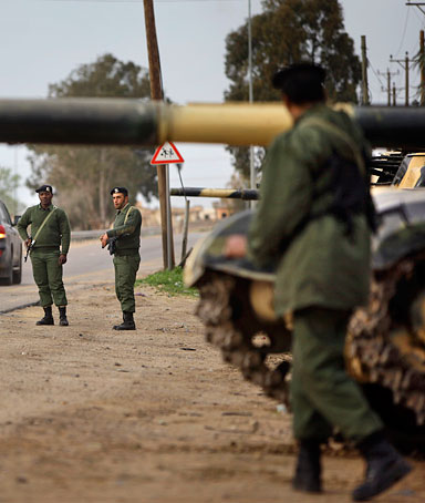 Soldiers and dozens of tanks from the Libyan military's elite Khamis Brigade take positions and check vehicles after arriving hours earlier on the road in Harshan, 10km east of Zawiya, in Libya, Monday, Feb. 28, 2011