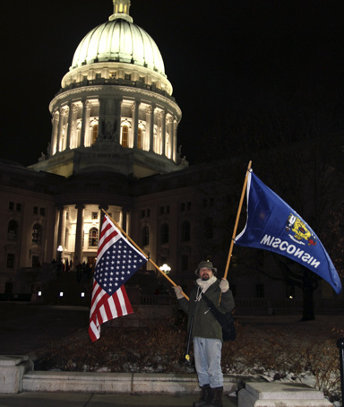 A protester holding the Wisconsin state flag and the U.S. national flag (L) stands in front of the Wisconsin State Capitol in Madison