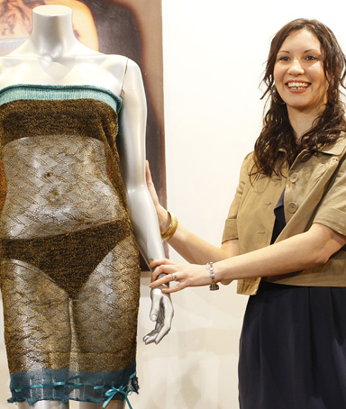 Charlotte Todd stands next to the dress she designed, and which was worn by Kate Middleton during a St Andrew's University charity fashion show in 2002, during a media event prior to its auction, in London, Wednesday, March, 16, 2011.