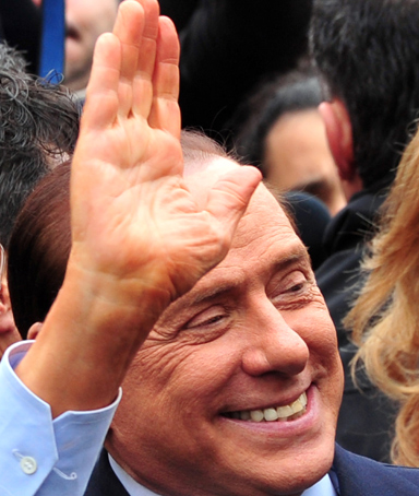 Italian Prime Minister Silvio Berlusconi waves to supporters as he leaves after for a legal hearing over allegations of fiscal fraud and breach of trust in his business interests on March 28, 2011 at Milan's justice court.