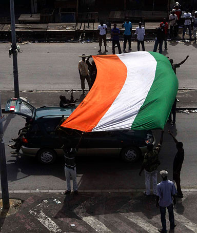 Fighters loyal to Ivory Coast presidential claimant Alassane Ouattara celebrate with a national flag in the main city Abidjan, April 11,2011.