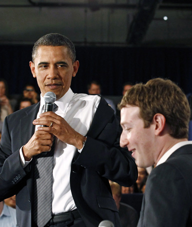U.S. President Barack Obama takes off his jacket as he attends a town hall meeting at Facebook headquarters with CEO Mark Zuckerberg in Palo Alto, April 20, 2011