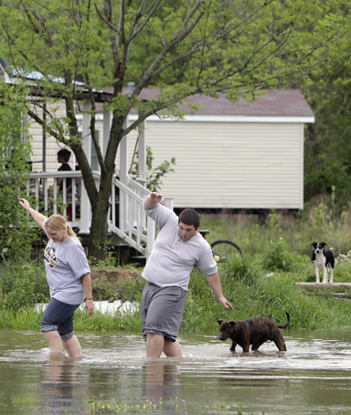 Eve Andrews, left, and her son Brandon Andrews walk through floodwater to get back to their home Monday, April 25, 2011, in Poplar Bluff, Mo.