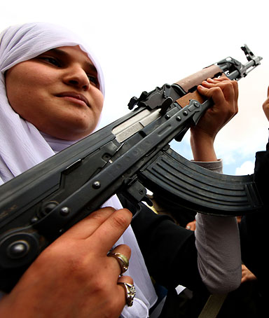 A Libyan student (L) holds a weapon as another waves a portrait of Libyan leader Moamer Kadhafi during a workshop presented by the army in Al-Sbeia, 65kms south of Tripoli, on April 27, 2011