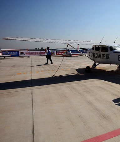 A policeman walks past a small general aircraft at the Neifu Airport during 2009 China International General Aviation Convention on October 17, 2009 in Pucheng County of Shaanxi Province, China