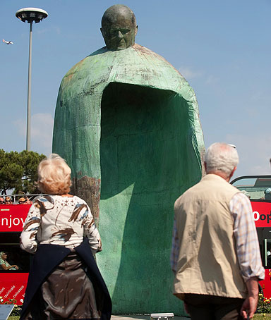 People look at a statue of Pope John Paul II, by Italian artist Oliviero Rainaldi, stands in front of the Termini train station, at Piazza dei Cinqucento on May 19, 2011 in Rome, Italy