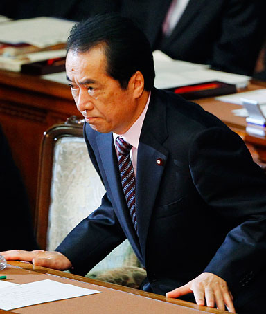 Japanese Prime Minister Naoto Kan leaves the plenary session at the lower house, after surviving a no-confidence motion against him in Tokyo, Japan, on  June 2, 2011